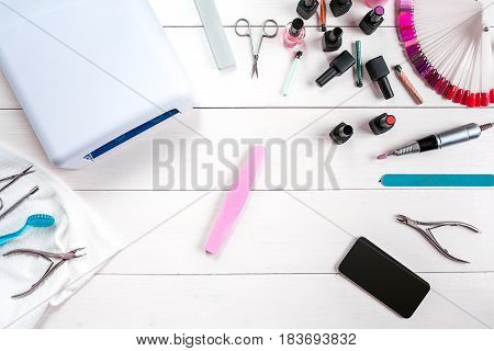 Manicure set and nail polish on wooden background. Close up. Top view. Copy space