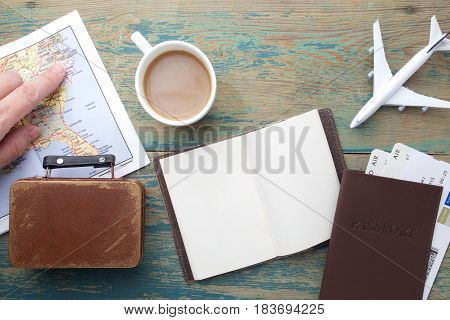 Travel , trip vacation, tourism mockup - close up note book, suitcase, toy airplane and touristic map on wooden table. Empty space you can place your text or information.