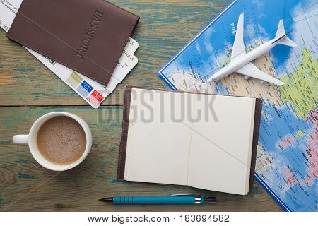 Travel , trip vacation, tourism mockup - close up note book, cup of coffee, toy airplane and touristic map on wooden table. Empty space you can place your text or information.