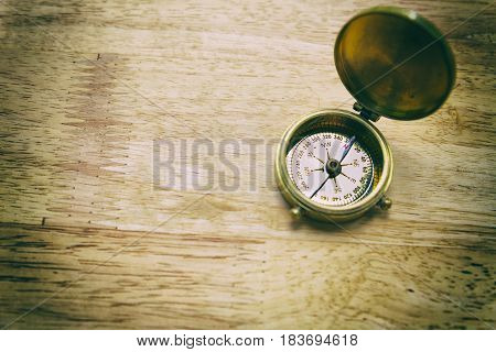 Antique Golden Compass On Wood Table. Concept For Direction, Travel, Guidance Or Assistance