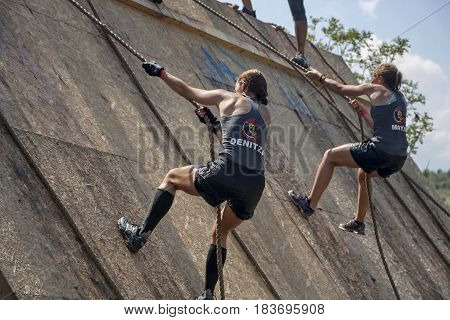 Two Women Climbing With Ropes On A Wall