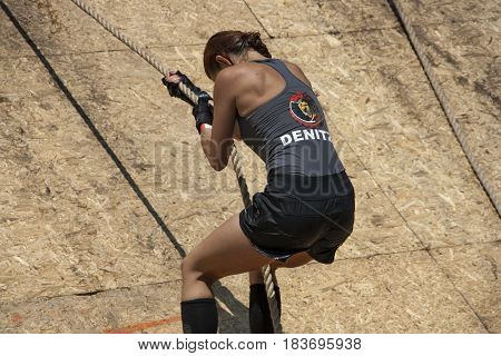 A Woman Climbing With A Rope On A Wall