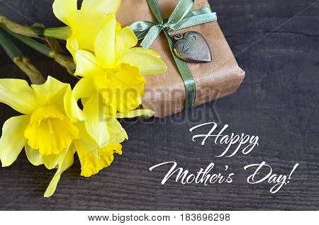 Happy Mother's Day.Bouquet of yellow Narcissus flowers and gift box with vintage silver heart on old wooden table.Spring flowers for Mother's Day.Soft selective focus.