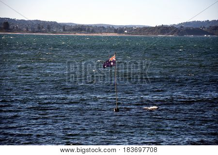 Australian flag waving in the water at Long Reef beach (Sydney NSW Australia).