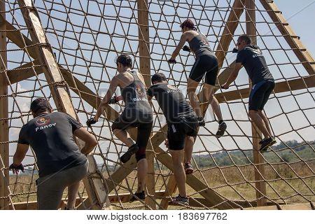 Team Of Men And Women Climbing Cargo Net