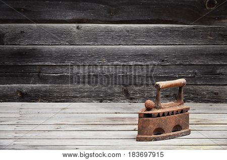 The Heavy And Rusty Old Coal Iron Lies On A Wooden Surface