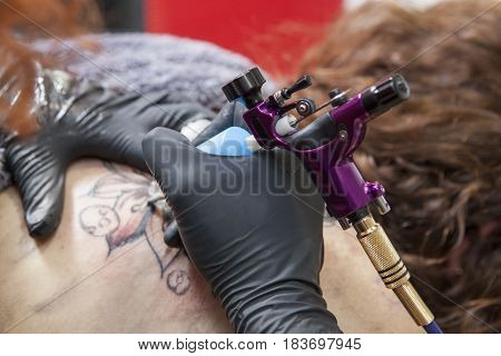 Tattoo artist applies tattoo to the shoulder blade of a woman. She is using a gun ink machine