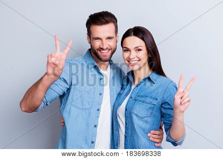 Photo Of Two Young Happy Smiling People In Jeans Shirts Isolated On Gray Background Giving V-sign
