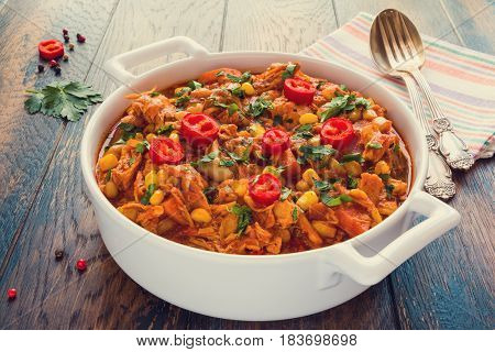 Hearty and healthy Southwest chicken and beans stew in a white casserole on the wooden table.