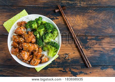 Chicken lacquered with a sweet soy teriyaki sauce in a white bowl. Garnished with rice and broccoli. Chopsticks brown wooden table top view.