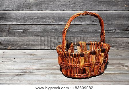 An Empty Wicker Basket Of Wooden Rods Lies On A Wooden Surface