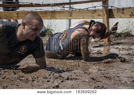 A Man And A Woman Crawling Under Barbed Wire