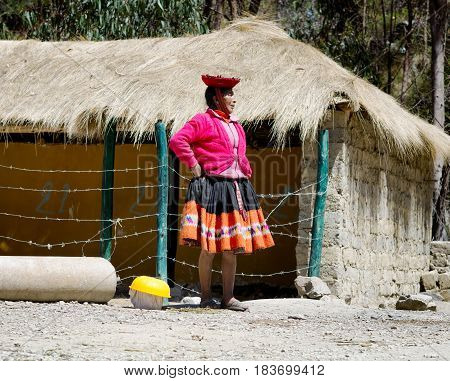 Quechua woman dressed in colourful traditional handmade outfit standing by barbed wire fence. October 21 2012 - Patachancha Cuzco Peru