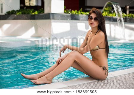 Woman in bikini sitting by the swimming pool. Spa. Recreation