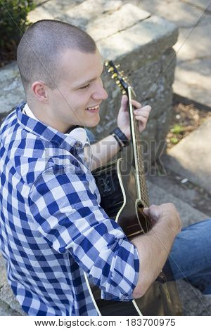 Portrait Of A Young Man With Guitar Outdoors