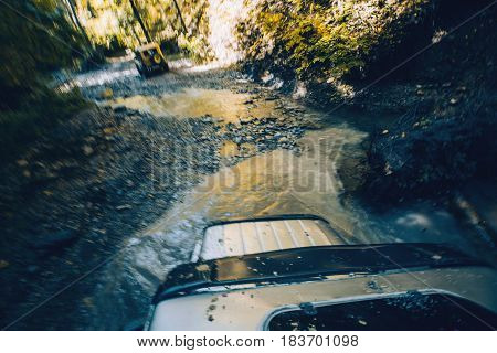 SUV cross the mountain river in forest. View from the hatch of the car. Tourist expedition Gelendzhik Russia