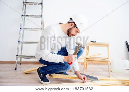 A man is hammering nails into a wood