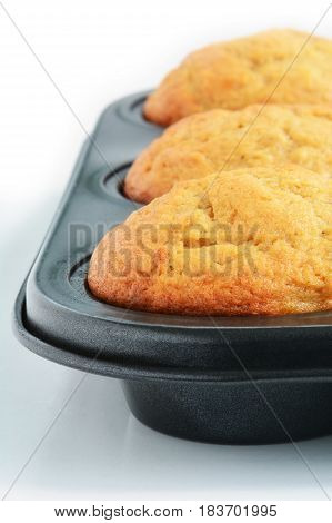 Fresh baked home made banana muffins in muffin tin. Vertical format with selective focus on front muffin.