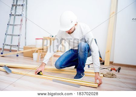 Young builder with a yellow measuring tape