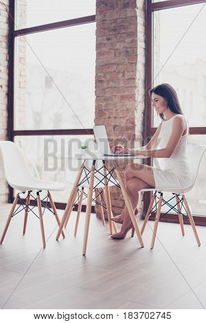 Full Size Portrait Of Young Smart Girl Typing On Her Laptop In The Cafe. She Is Wearing Smart White