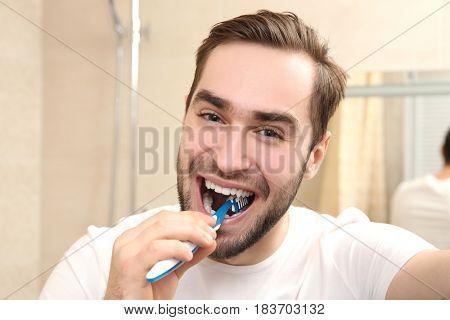 Handsome man brushing teeth in bathroom