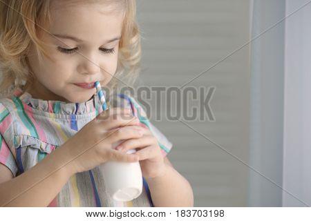 Cute little girl drinking yogurt at home