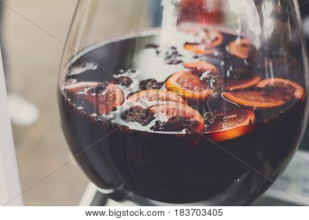 Making hot alcohol, mulled wine for sale at country fair. Glintwine from red wine with citrus and cloves in big glass, Closeup