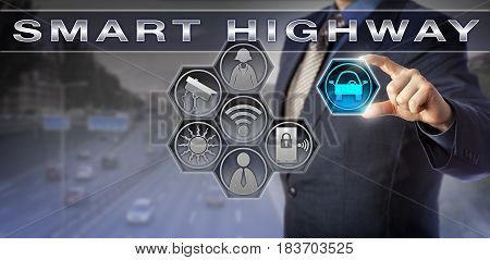 Blue chip corporate manager is plugging an automobile icon into a SMART HIGHWAY monitoring interface. Information technology concept for traffic management mobility management and smart integration.
