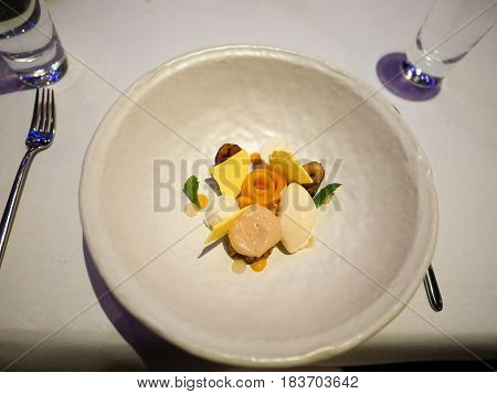 Dessert served in shape of a flower surrounded by ice creams in fine dining restaurant.