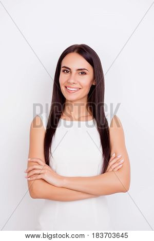 Close Up Portrait Of Young Successful Girl In White Dress On White Background Standing With Crossed