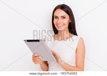 Young Smiling Brunette Woman Holding Tablet And Typing On It. She Is Smiling, Wearing White Clothes