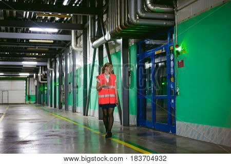 Female Employee In An Orange Robe Vest In The Working Space Of A Production Facility, Exercises Cont