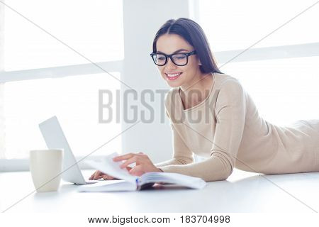Cute Smart Girl In Glasses Lies On The White Floor And Turns Over The Pages The Diary, The Laptop An