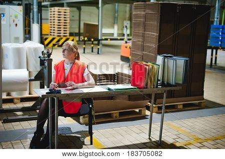 Portrait Of A Female Employee In An Orange Robe Vest In The Working Space Of A Production Facility,