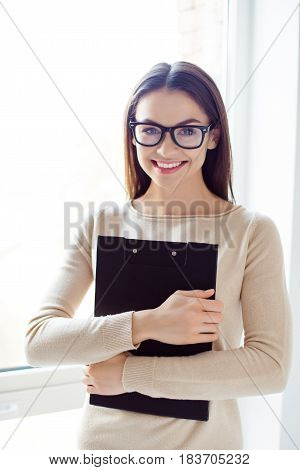 Portrait Of Young Cute Pretty Woman In Glasses Stands Sideways In The Office Near The Window, Holds