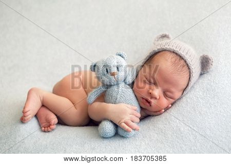 Newborn boy in a hat lies on a light blanket with a blue knitted bear