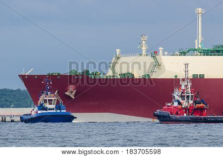 LNG TANKER, TUG AND FIREBOAT-  Gas Carrier safety secured by fireboat at the gas terminal in the port
