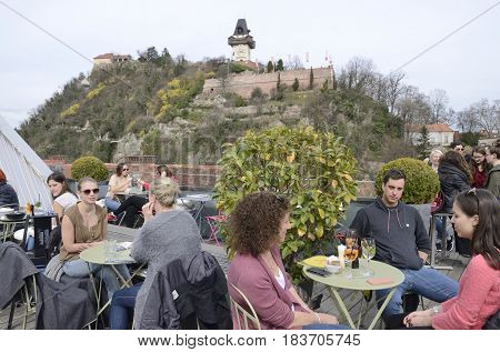 GRAZ, AUSTRIA - MARCH 20, 2017: People at the terrace of the Kastner and Ohler warehouses with views to Tower of the Clock in Graz the capital of federal state of Styria Austria.
