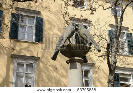 Sculptures of doves and yellow building in Graz the capital of federal state of Styria Austria.