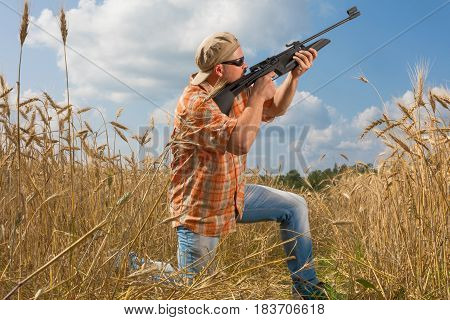 Hunter at cap and sunglasses aiming a gun at field