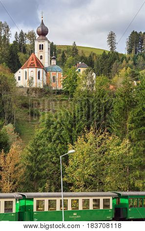 KOGLHOF/ AUSTRIA - OCTOBER 9, 2016. View of the old church Sankt Georgen am Gasenbach and narrow gauge railway wagon Feistritztalbahn in the village of Koglhof. Municipality Birkfeld, Styria, Austria.
