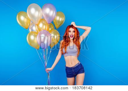 Funny Carefree Girl With Ginger Hair Holding Many Of Colorful Balloons And Celebrating Holiday While