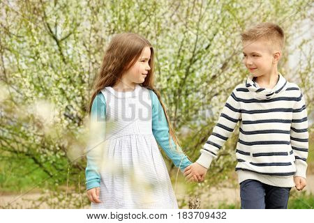 Pretty little girl and cute boy walking in spring park