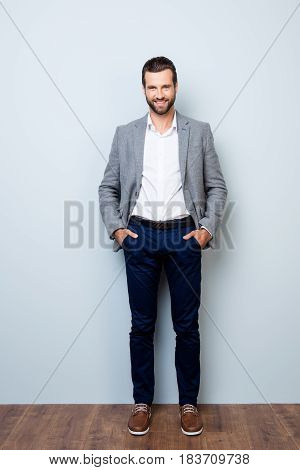 Vertical Full-length Portrait Of Handsome Smiling Happy Successful Businessman Holding His Hands In
