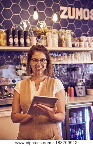 Mature Lady Behind Coffee Shop Counter