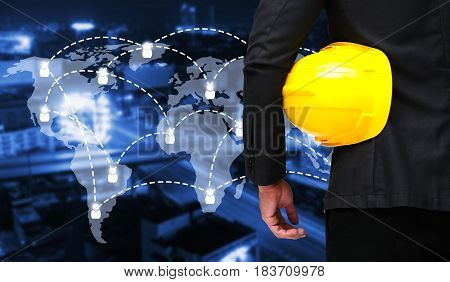 businessman with yellow safety helmet with world map social media network connection on blurred night city background industrial business and technology concept
