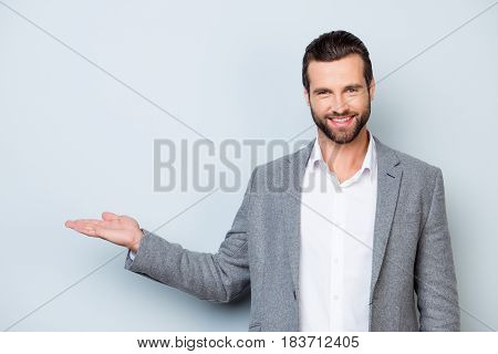 Handsome Smiling Young Man In Jacket Showing On Copyspace With His Hand