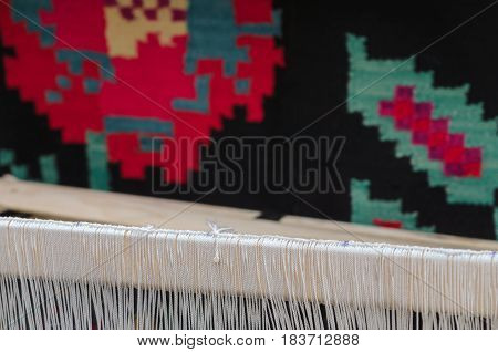 The background of the carpet is made of wool and the warp threads on the loom. Bazaar trade, selective focus.