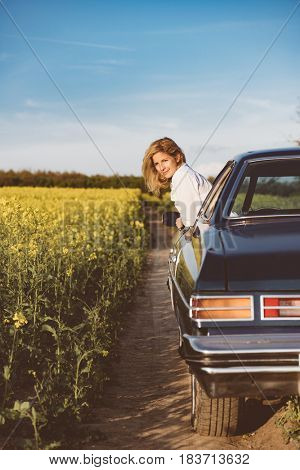 Young woman resting in car window during road trip.