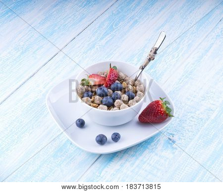 Healthy breakfast concept with oat flakes and fresh berries on rustic background. Healthy snack, fitness food, yogurt with musli and dried fruit, nutrition for weightloss, breakfast. Food made of granola and musl a blue wooden table top view.